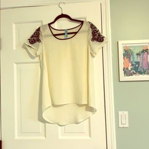 White top with navy embroidery on the sleeves